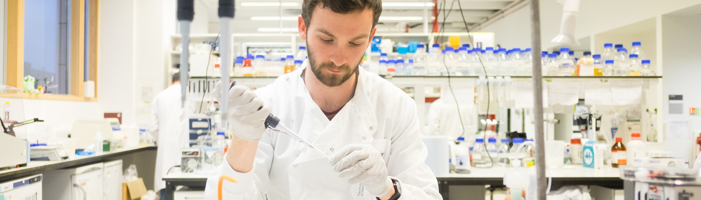 Researcher wearing whtie lab coat surrounded by blue capped bottles squeezing pipette into tube